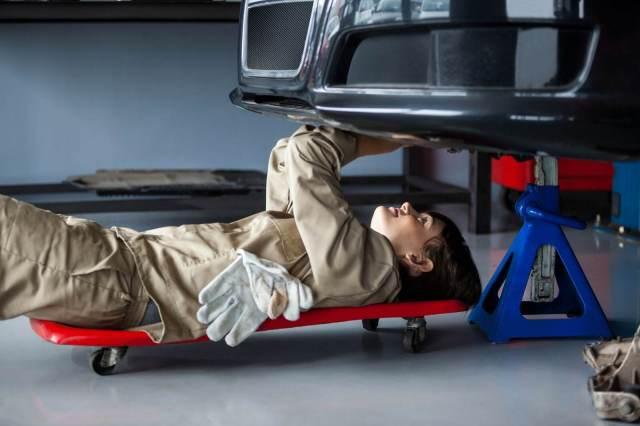 mecânica deitada sobre um carrinho embaixo do veículo
