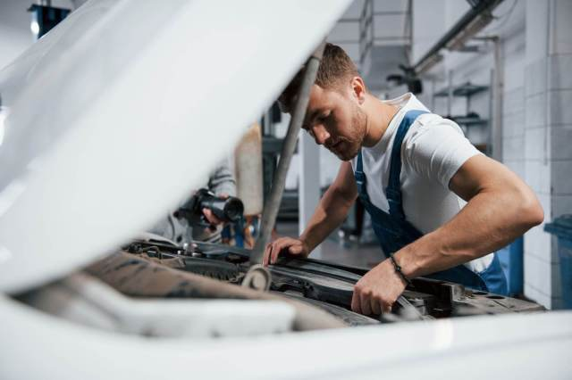 homem olhando o motor do carro