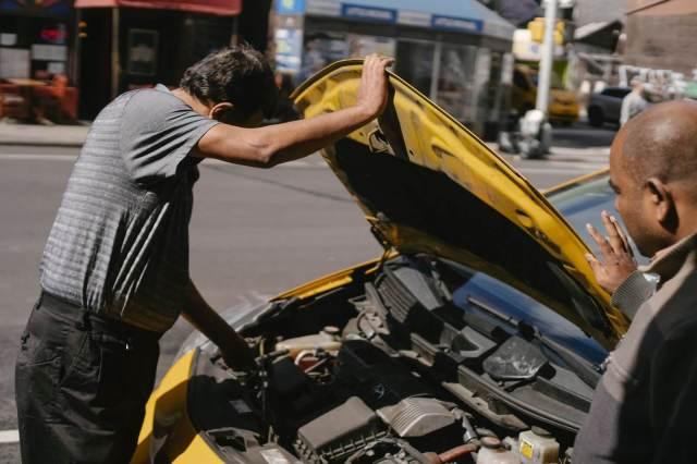 carro amarelo com capô aberto, no meio da rua. Dois homens verificando o problema