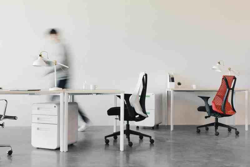 mujer en oficina con dos escritorios vacíos
