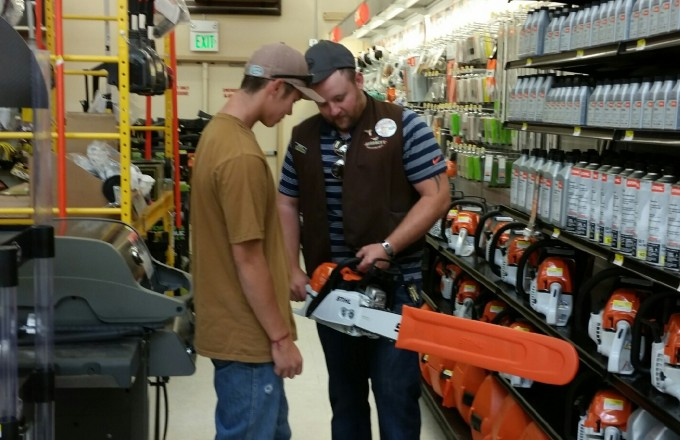 Assistant Store Manager, Stetson Mumma, helping a customer with chainsaws