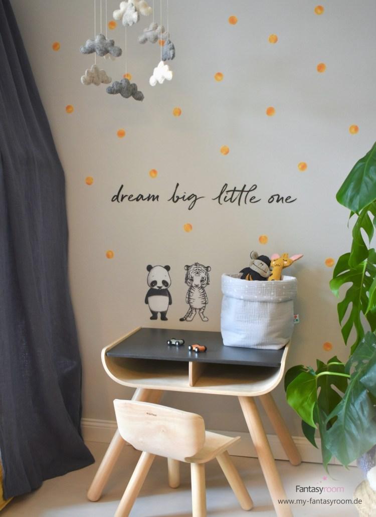 Kinderzimmer mit senfgelben Punktestickern an der grauen Wand und Sitzgruppe von Plantoys