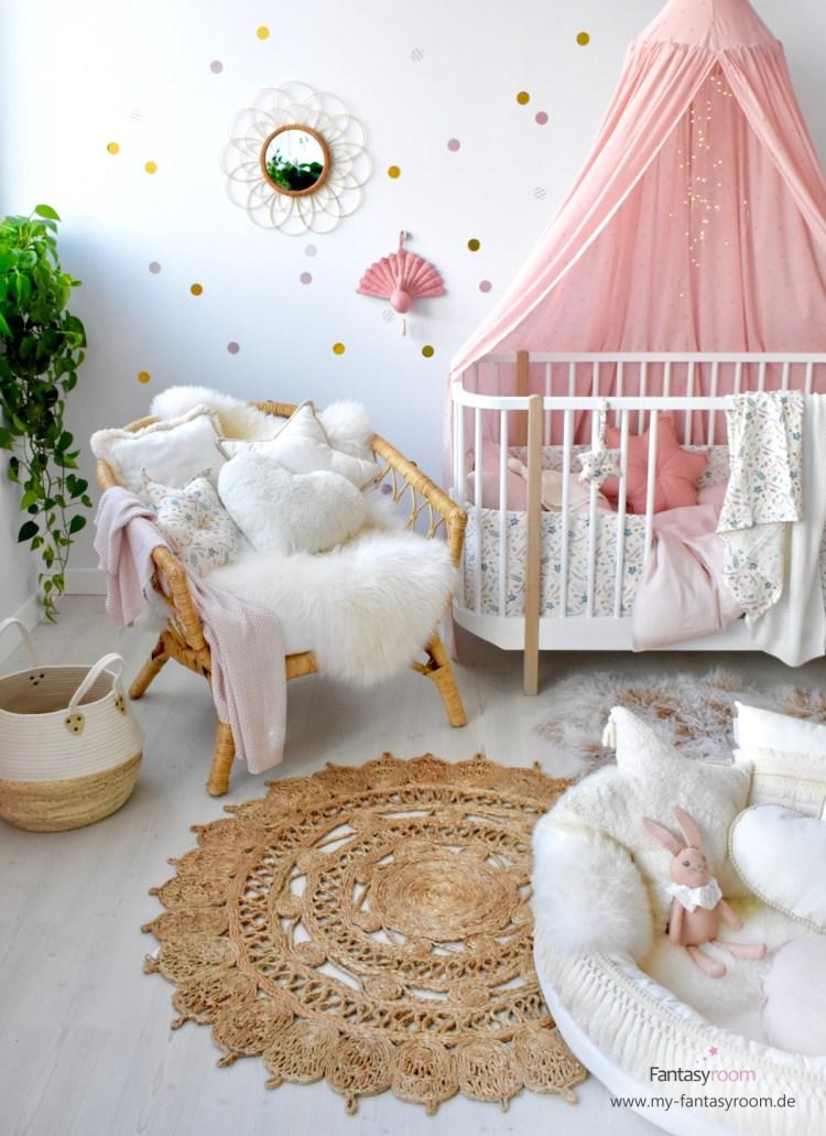 Babyzimmer mit Babybett und gemütlicher Sitzecke, mit kuscheligen Textilien, Fellen und Juteteppich eingerichtet