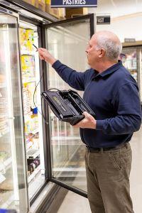 Refrigeration contractor locating refrigerant leak in supermarket.