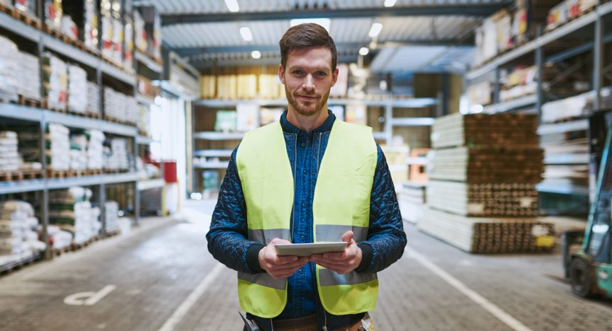 Refrigeration contractor standing with tablet in warehouse.