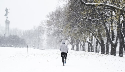 Man walking or jogging in the snow in winter