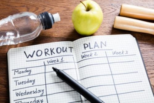 Workout plan in diary fitness planning concept