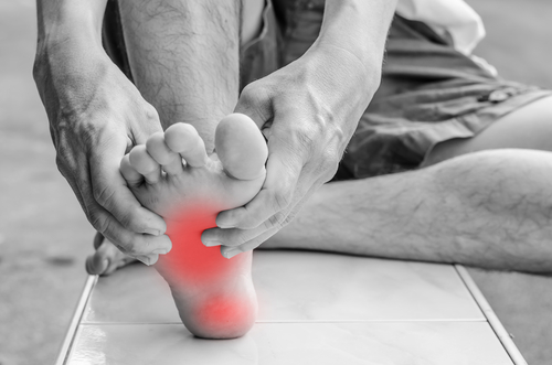 Holding painful foot - arch pain concept