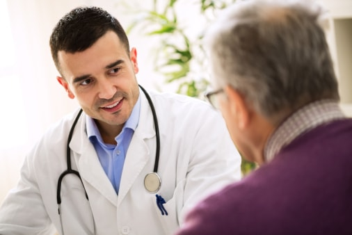 Senior man talking to doctor about health
