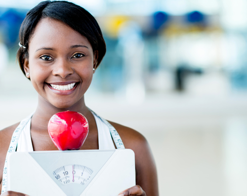 Woman holding scale and apple - healthy weight concept
