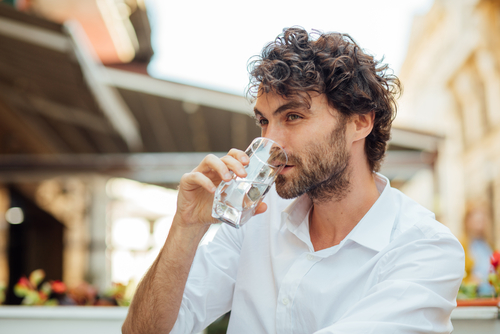 Man drinking water at an outdoor cafe