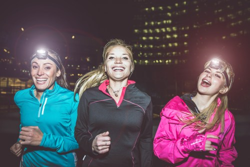 Women running at night with headlamps