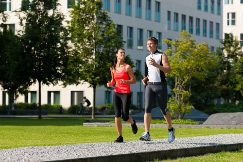 Couple jogging for fitness in a sunny urban park