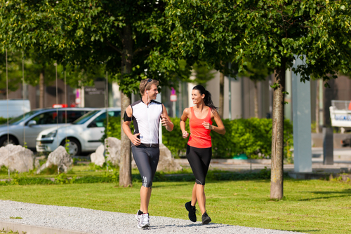 Couple jogging for fitness in a green city park