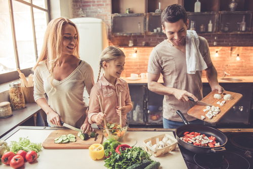 Family cooking dinner together in kitchen