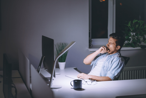 Man working late yawning in front of a computer