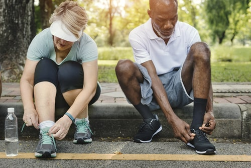 Man and woman tying shoes before a fitness walk