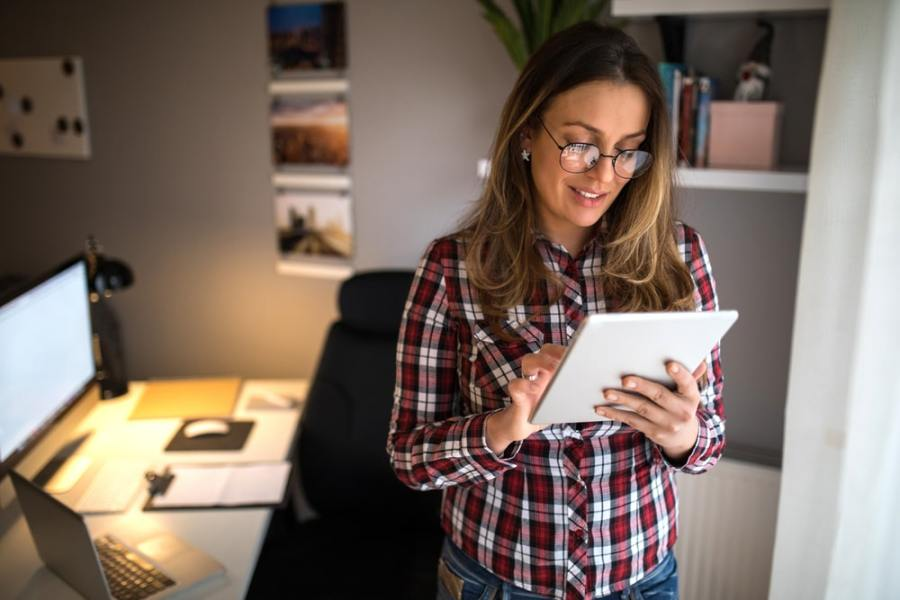 Woman standing up to burn calories working from home