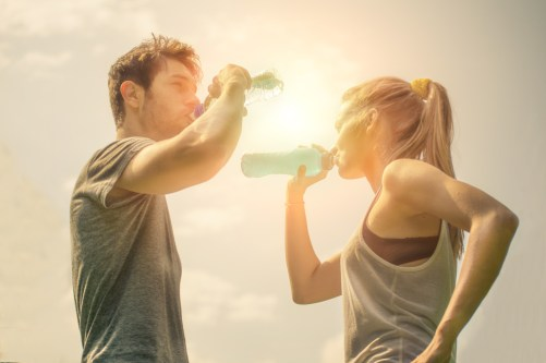 Couple drinking water while walkingMan and woman drinking water while walking