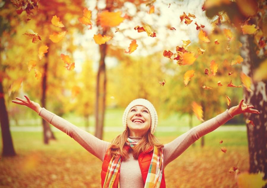 Happy female walker throwing leaves