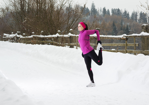 Woman stretching in snow