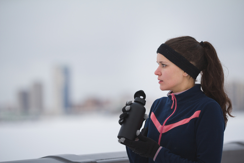 Female jogger drinking from water bottle