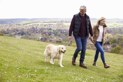 Couple walking dog in hilly terrain