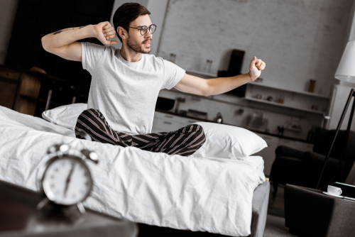 Man waking up with alarm clock