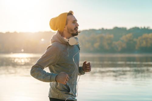 Man fitness walking with headphones near water