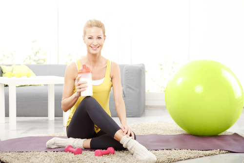 Woman holding a protein shake after stretching
