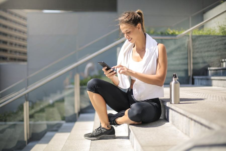 Athletic woman checking her phone after run
