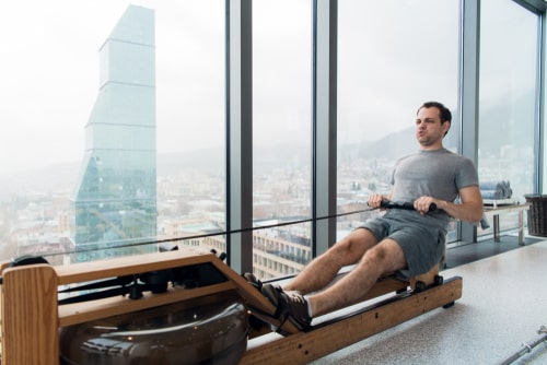Man in high-rise using rowing machine
