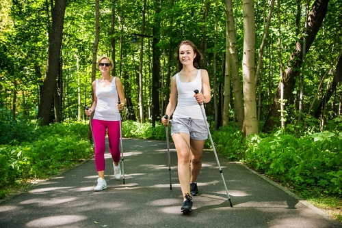 Women power walking with poles in the park