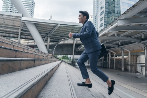 Businessman in dress clothes running up stairs