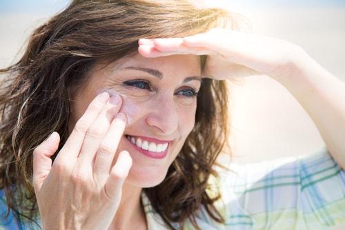 Woman applying sunscreen in summer