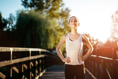 Happy woman standing next to bridge after walking