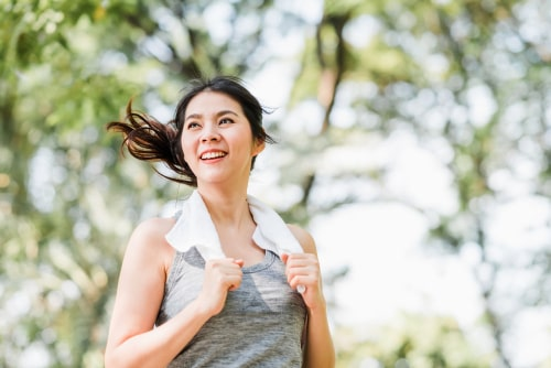 Woman smiling and holding towel after walking
