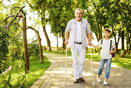 Senior man walking with cane and grandson