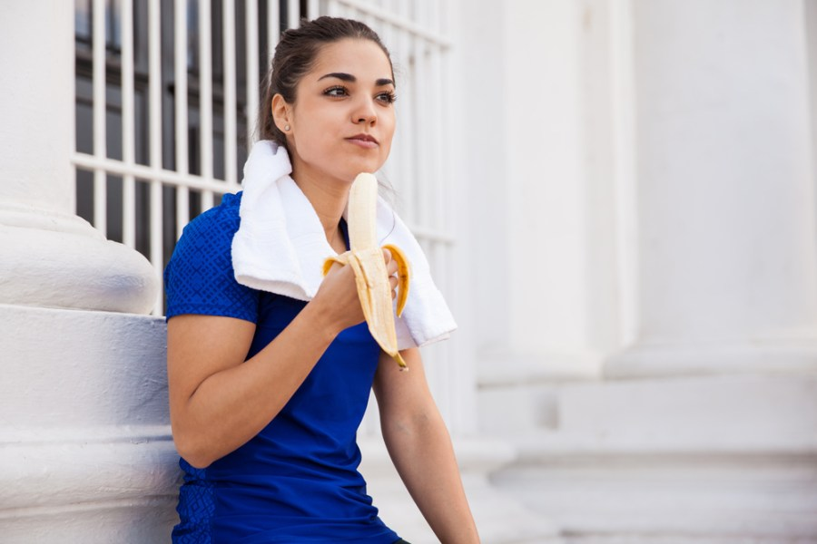 Female athlete eating a banana after a workout