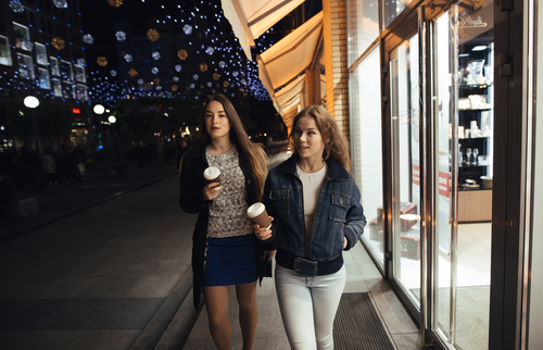 Women walking with coffee in the city at night