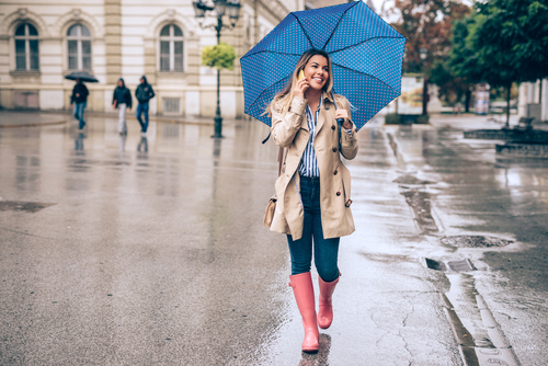 Woman walking in the rain and talking on phone
