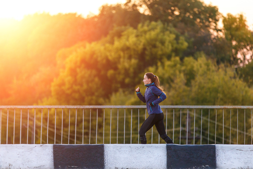 Woman jogging over a bridge in the park