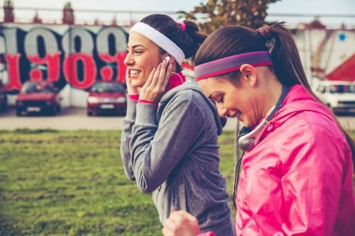 Women running together listening to headphones