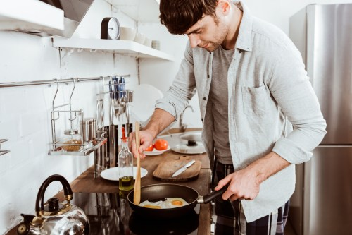 Man cooking eggs for breakfast