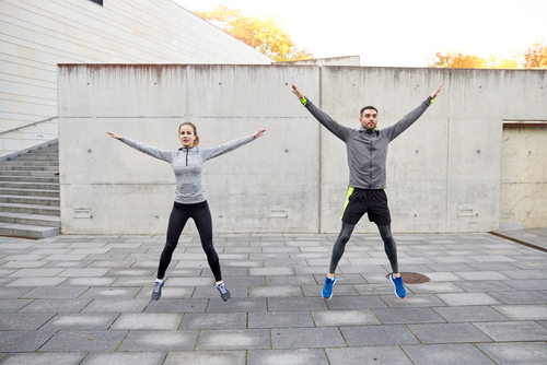 Couple doing jumping jacks outside