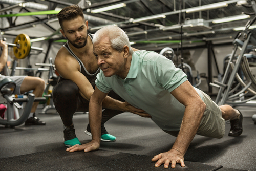 Coach helping an older man do perfect pushups