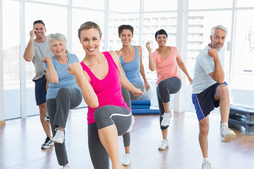 Men and women doing a group fitness class