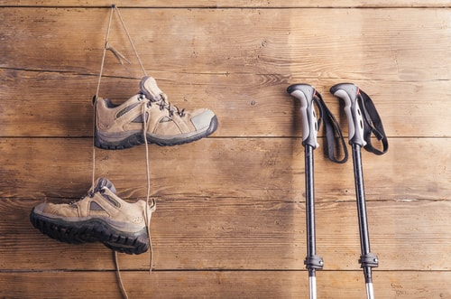 Walking shoes and Nordic walking poles on wall