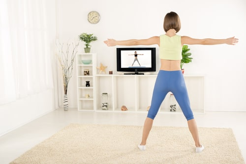 Woman doing exercises in front of tv at home