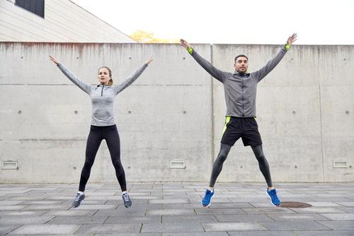 Couple doing jumping jacks outside